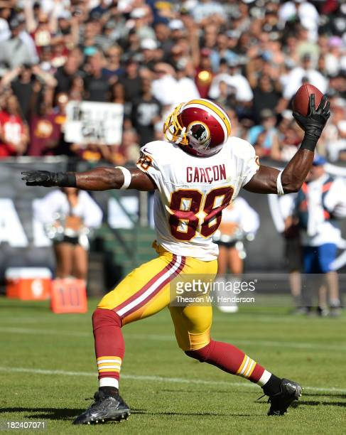 Pierre Garcon of the Washington Redskins slams the ball down after he caught a five yard touchdown pass during the third quarter against the Oakland...