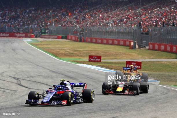 Pierre Gasly of France and Scuderia Toro Rosso driving the Scuderia Toro Rosso STR13 Honda leads Daniel Ricciardo of Australia driving the Aston...