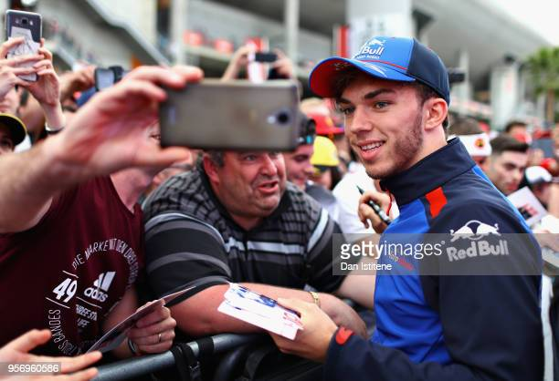 Pierre Gasly of France and Scuderia Toro Rosso poses for a photo with a fan during previews ahead of the Spanish Formula One Grand Prix at Circuit de...