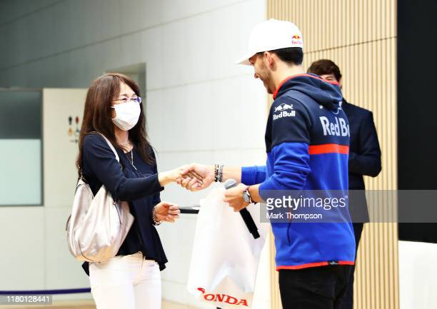 Pierre Gasly of France and Scuderia Toro Rosso presents a fan with a goodie bag during previews ahead of the F1 Grand Prix of Japan at Honda Proving...