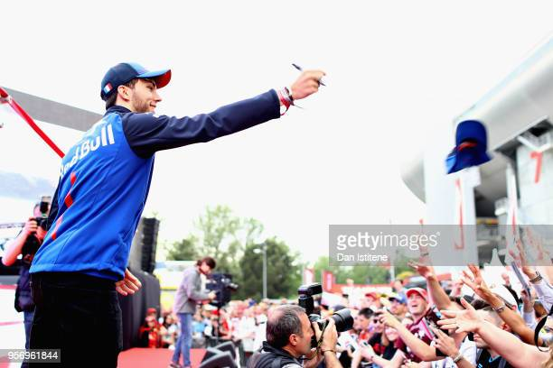 Pierre Gasly of France and Scuderia Toro Rosso throws a cap to fans during previews ahead of the Spanish Formula One Grand Prix at Circuit de...