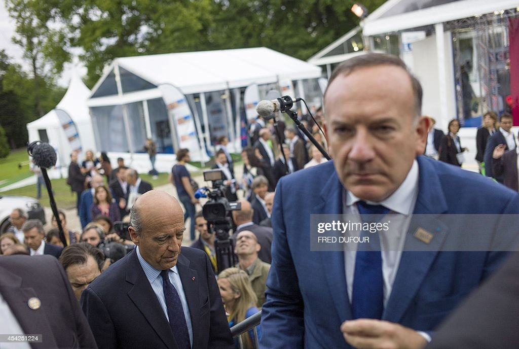 Pierre Gattaz (R), president of French employers' association Medef, arrives with Alain Juppe (L), mayor of Bordeaux, interim president part of a triumvirate leading the French right-wing UMP party and candidate for the UMP primary election for the 2017 French presidential elections, at the Medef summer conference on August 27, 2014 in Jouy-en-Josas, southwest of Paris.
