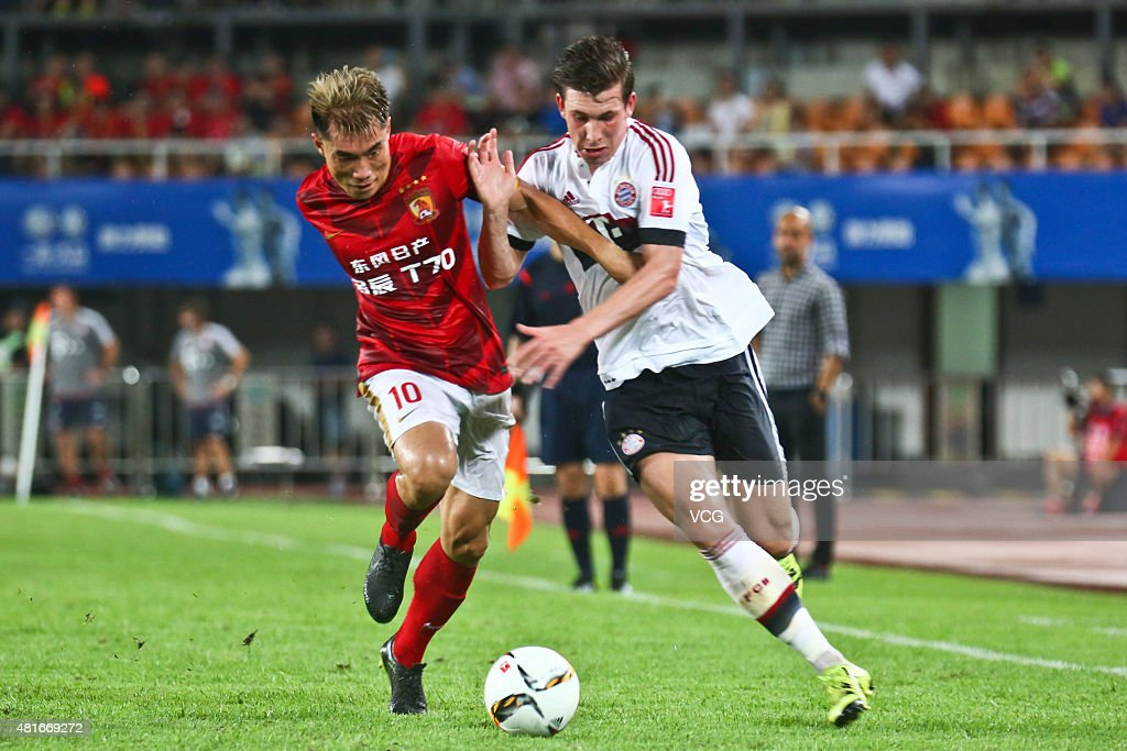 Pierre Hojbjerg #34 of FC Bayern Muenchen and Zheng Zhi #10 of Guangzhou Evergrande compete for the ball during the international friendly match between Guangzhou Evergrande and FC Bayern Muenchen of the Volkswagen Cup Guangzhou at Tianhe Stadium on July 23, 2015 in Guangzhou, China.