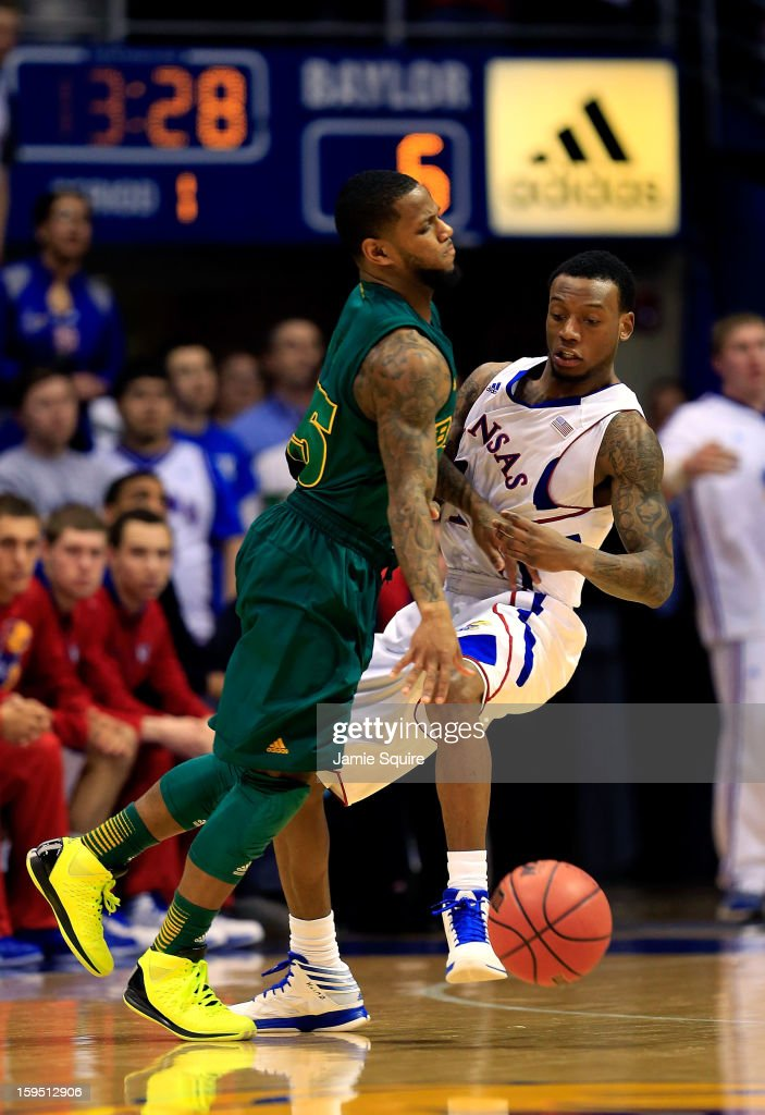 Pierre Jackson #55 of the Baylor Bears drives as Naadir Tharpe #1 of the Kansas Jayhawks defends during the game at Allen Fieldhouse on January 14, 2013 in Lawrence, Kansas.