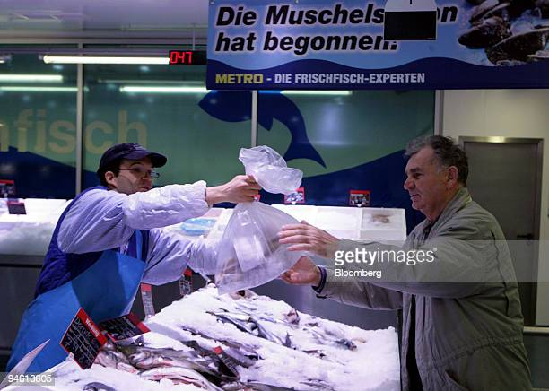 Pierre Laufs a Metro employee left hands some fresh fish to a customer inside a Metro wholesale store in Duesseldorf Germany on Tuesday Jan 8 2008...