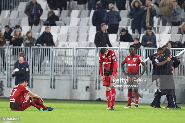 Pierre Lees Melou Mehdi Abeid and Arnold Bouka Moutou of Dijon look dejected as Francois Kamano of Bordeaux celebrates with his teammates during the...