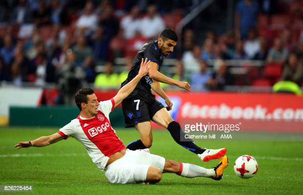 Pierre LeesMelou of OGC Nice is tackled by Nick Viergever of Ajax during the UEFA Champions League Qualifying Third Round match between Ajax and OSC...