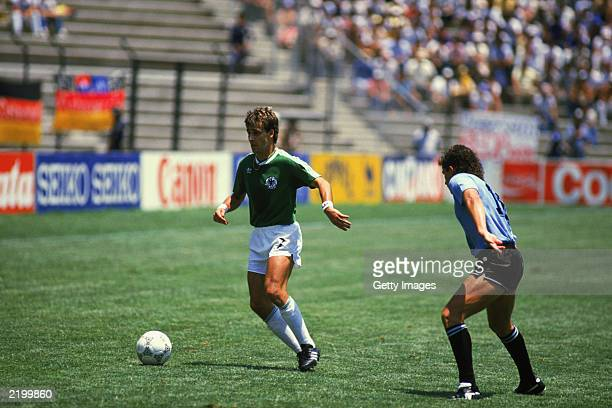Pierre Littbarski of West Germany looks to take the ball past Sergio Santin of Uruguay during the FIFA World Cup Finals 1986 Group E match between...