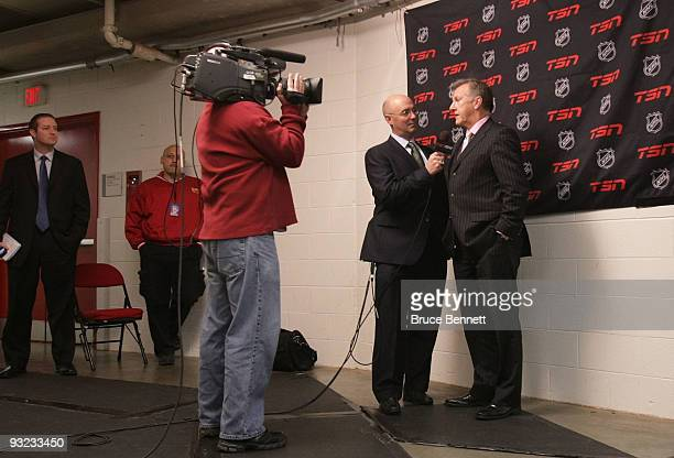 Pierre McGuire interviews head coach Ron Wilson of the Toronto Maple Leafs prior to the game against the Carolina Hurricanes at the RBC Center on...