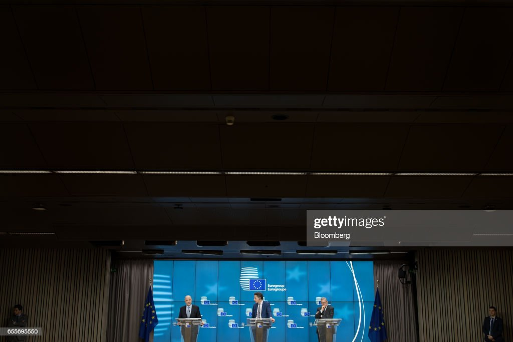 Pierre Moscovici, economic commissioner for the European Union (EU), from left, Jeroen Dijsselbloem, Dutch finance minister and head of the group of euro-area finance ministers, and Klaus Regling, managing director of the European Stability Mechanism, stand during a news conference following a Eurogroup meeting of finance ministers in Brussels, Belgium, on Monday, March 20, 2017. Wolfgang Schaeuble, Germany's finance minister, said to reporters ahead of the meeting of euro-area finance ministers We'll get a report on Greece, but the mission isn't completed. Photographer: Jasper Juinen/Bloomberg via Getty Images