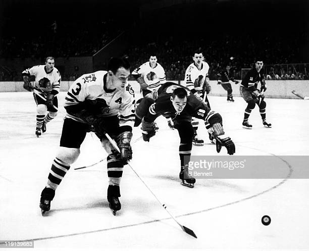 Pierre Pilote of the Chicago Blackhawks battles for the puck with Danny Belisle of the New York Rangers during their game on October 19 1960 at the...