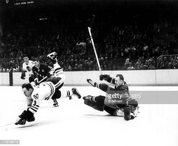 Pierre Pilote of the Chicago Blackhawks dives for the puck as Reggie Fleming of the New York Rangers crashes into goalie Denis DeJordy of the...