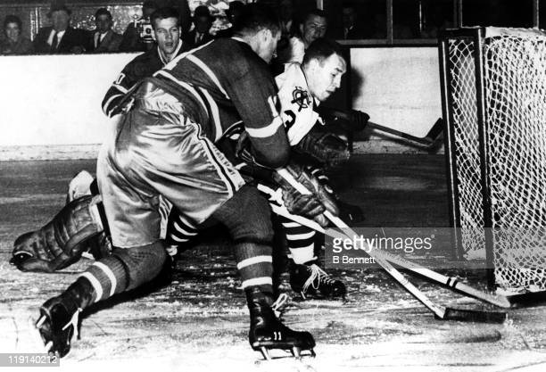 Pierre Pilote of the Chicago Blackhawks poke checks the puck away from Tom Johnson of the Montreal Canadiens during their game on October 17 1959 at...