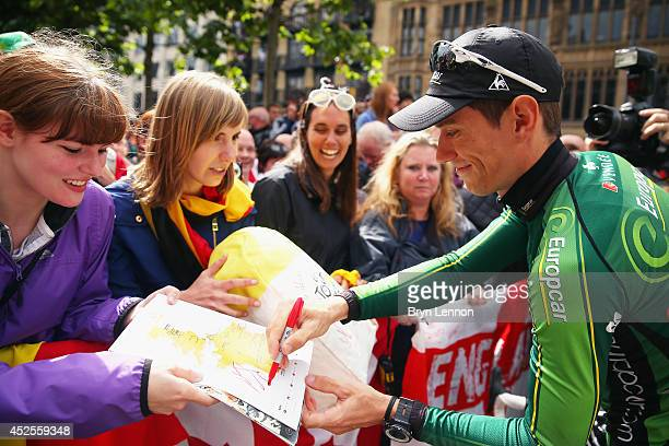 Pierre Rolland of France and Team Europcar signs autographs ahead of the first stage of the 2014 Tour de France a 190km stage between Leeds and...