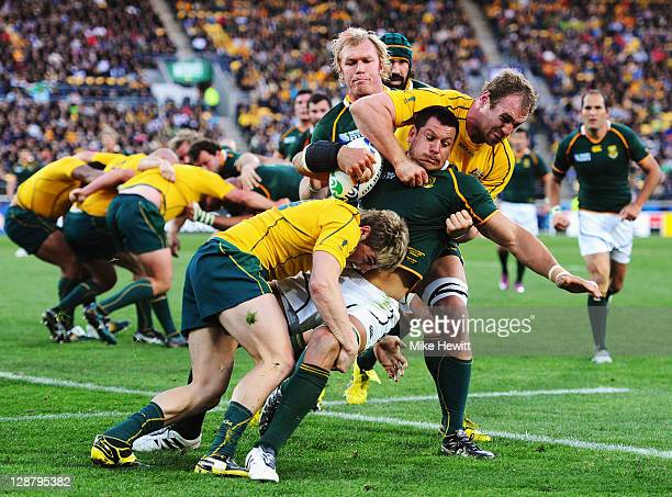Pierre Spies of South Africa is tackled by James O'Connor and Rocky Elsom of Australia during quarter final three of the 2011 IRB Rugby World Cup...