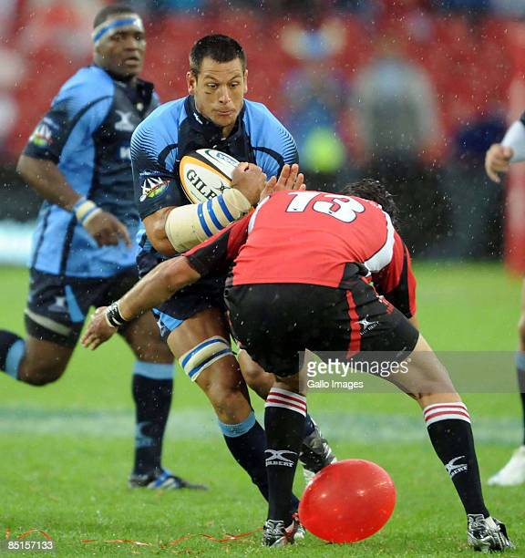 Pierre Spies of the Bulls is tackled by Jaques Fourie during the round three Super 14 match between the Lions and Bulls at Coca-Cola Park on February...