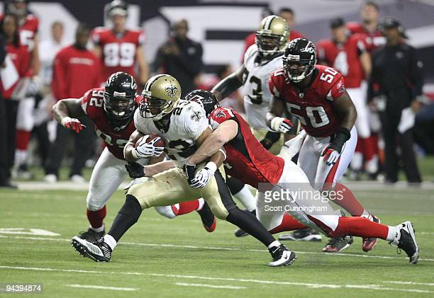 Pierre Thomas of the New Orleans Saints carries the ball against Kroy Biermann of the Atlanta Falcons at the Georgia Dome on December 13, 2009 in...