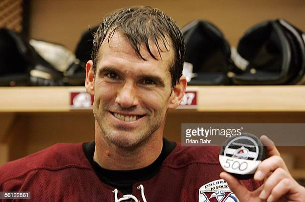 Pierre Turgeon of the Colorado Avalanche holds up the puck from his 500th career goal against goalie Vesa Toskala of the San Jose Sharks in the third...