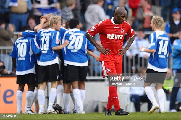 Pierre Wome of Koeln looks dejected while players of Bielefeld celebrate their second goal during the Bundesliga match between Arminia Bielefeld and...