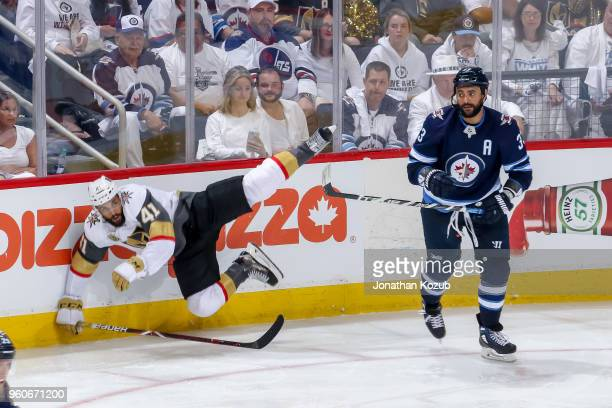 PierreEdouard Bellemare of the Vegas Golden Knights falls to the ice after being checked by Dustin Byfuglien of the Winnipeg Jets during third period...