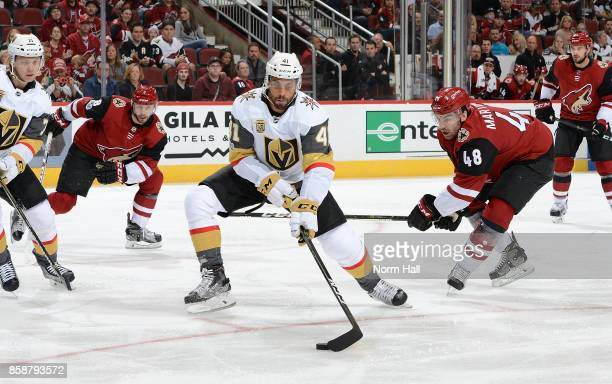 PierreEdouard Bellemare of the Vegas Golden Knights skates with the puck past Jordan Martinook of the Arizona Coyotes during the first period at Gila...