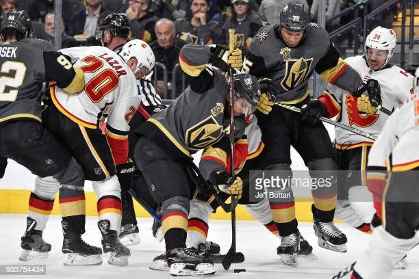 PierreEdouard Bellemare Ryan Reaves and Tomas Nosek of the Vegas Golden Knights battle for the puck with Curtis Lazar and Travis Hamonic of the...