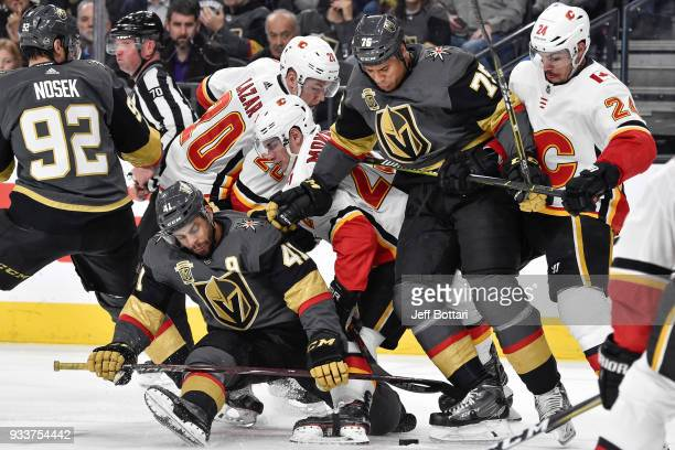 PierreEdouard Bellemare Ryan Reaves and Tomas Nosek of the Vegas Golden Knights battle for the puck with Curtis Lazar Sean Monahan and Travis Hamonic...