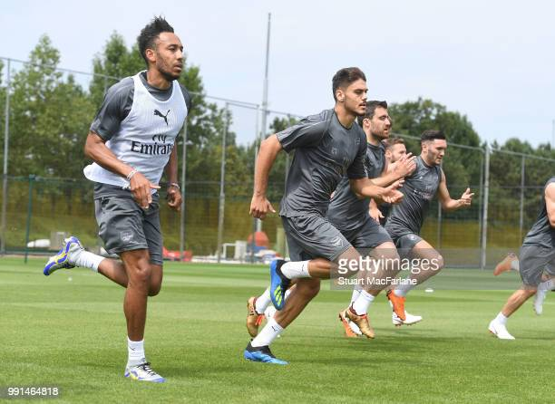 PierreEmerick Aubameyang and Konstantinos Mavropanos of Arsenal run during a training session at London Colney on July 4 2018 in St Albans England