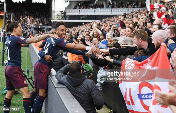PierreEmerick Aubameyang celebrates scoring the 4th Arsenal goal with the fans during the Premier League match between Fulham FC and Arsenal FC at...