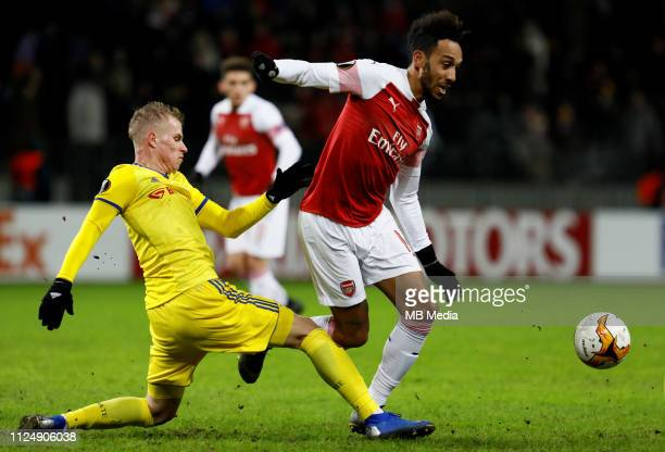 PierreEmerick Aubameyang of Arsenal and Evgeni Berezkin of BATE Borisov vie for the ball during the UEFA Europa League Round of 32 First Leg match...
