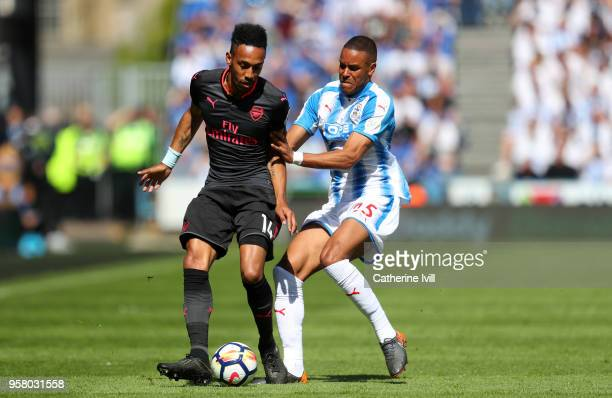 PierreEmerick Aubameyang of Arsenal and Mathias Jorgensen of Huddersfield Town battle for possession during the Premier League match between...