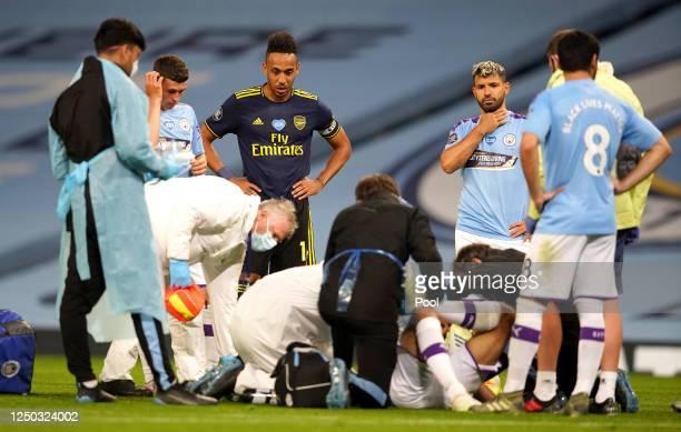 PierreEmerick Aubameyang of Arsenal and Sergio Aguero of Manchester City react as Eric Garcia of Manchester City receives medical treatment during...