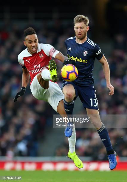 PierreEmerick Aubameyang of Arsenal battles for possession in the air with Tim Ream of Fulham during the Premier League match between Arsenal FC and...
