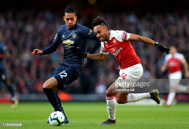 PierreEmerick Aubameyang of Arsenal battles for possession with Chris Smalling of Manchester United during the Premier League match between Arsenal...
