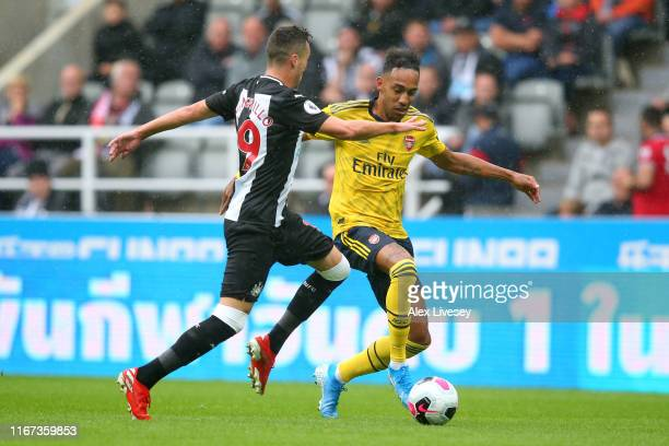 PierreEmerick Aubameyang of Arsenal battles for possession with Javier Manquillo of Newcastle United during the Premier League match between...