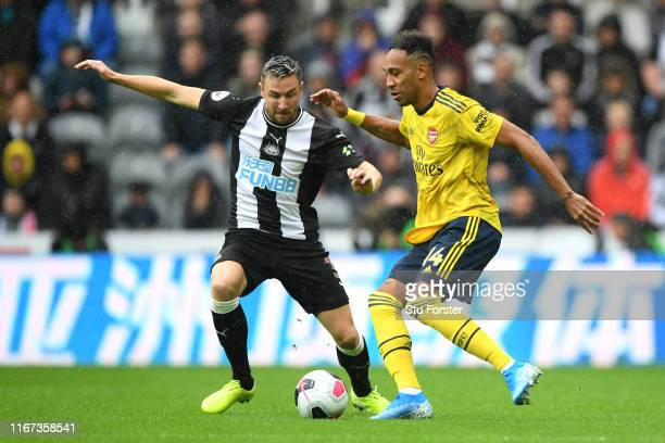 PierreEmerick Aubameyang of Arsenal battles for possession with Paul Dummett of Newcastle United during the Premier League match between Newcastle...