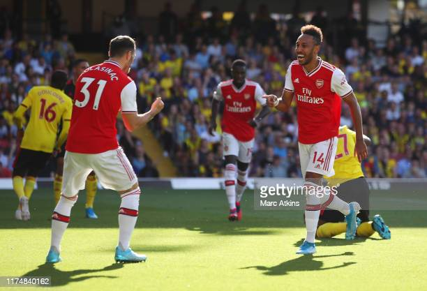 PierreEmerick Aubameyang of Arsenal celebrates as he scores his team's first goal with Sead Kolasinac during the Premier League match between Watford...