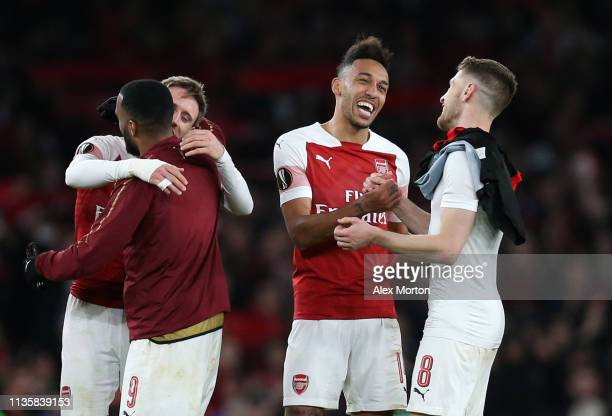 PierreEmerick Aubameyang of Arsenal celebrates victory with teammate Aaron Ramsey after the UEFA Europa League Round of 16 Second Leg match between...