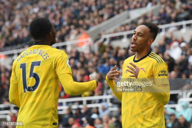 PierreEmerick Aubameyang of Arsenal celebrates with teammate Ainsley MaitlandNiles after scoring his team's first goal during the Premier League...