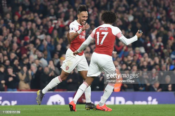 PierreEmerick Aubameyang of Arsenal celebrates with teammate Alex Iwobi after scoring his team's fourth goal during the Premier League match between...