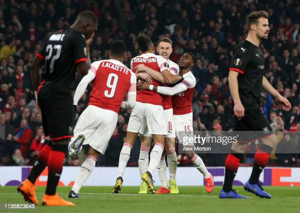 PierreEmerick Aubameyang of Arsenal celebrates with teammates Aaron Ramsey and Ainsley MaitlandNiles after scoring his team's first goal during the...
