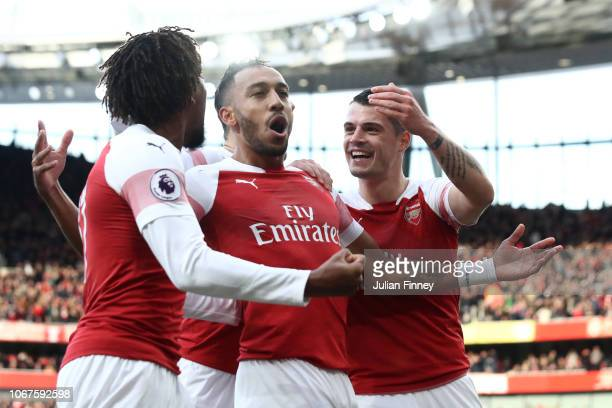 PierreEmerick Aubameyang of Arsenal celebrates with teammates after scoring his team's first goal during the Premier League match between Arsenal FC...