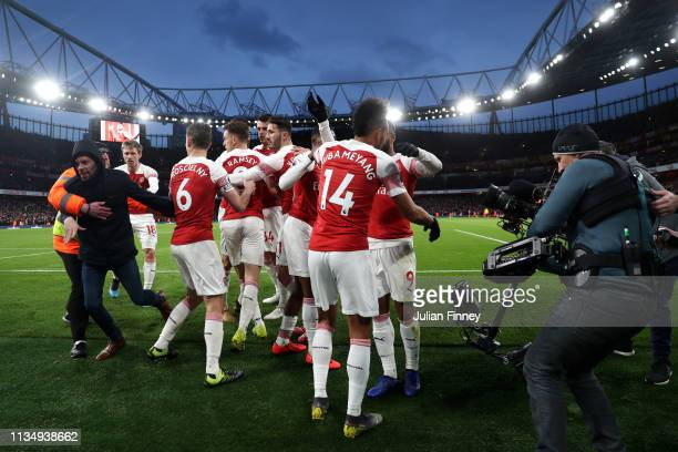 PierreEmerick Aubameyang of Arsenal celebrates with teammates after scoring his team's second goal as a pitch invader is escorted away by stewards...