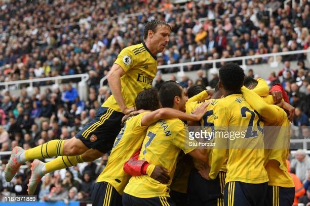 PierreEmerick Aubameyang of Arsenal celebrates with teammates as Nacho Monreal jumps on top after scoring his team's first goal during the Premier...