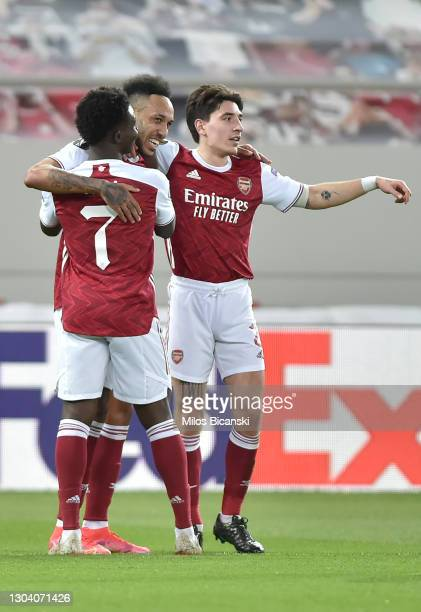 Pierre-Emerick Aubameyang of Arsenal celebrates with teammates Bukayo Saka and Hector Bellerin after scoring his team's first goal during the UEFA...