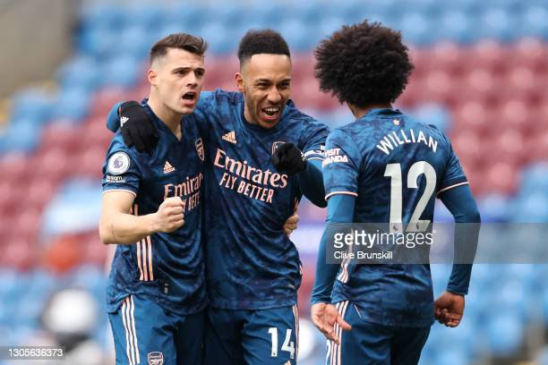 Pierre-Emerick Aubameyang of Arsenal celebrates with teammates Granit Xhaka and Willian after scoring his team's first goal during the Premier League...