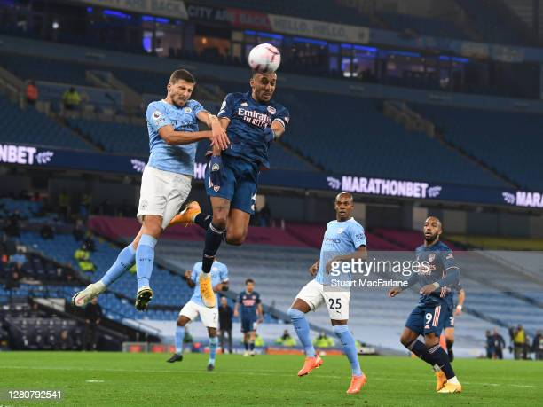 PierreEmerick Aubameyang of Arsenal challenged by Ruben Dias of Man City during the Premier League match between Manchester City and Arsenal at...