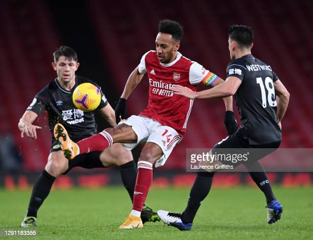 Pierre-Emerick Aubameyang of Arsenal controls under pressure from James Tarkowski and Ashley Westwood of Burnley during the Premier League match...