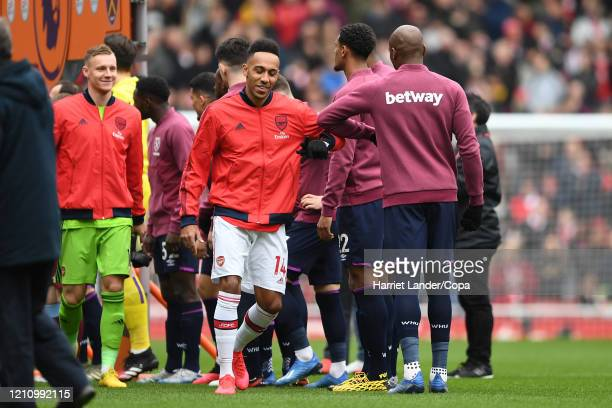 PierreEmerick Aubameyang of Arsenal greets West Ham United players with his elbow over fears about the coronavirus prior to the Premier League match...