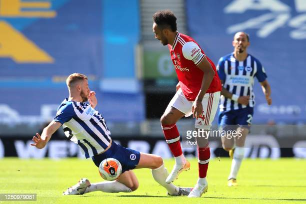 PierreEmerick Aubameyang of Arsenal is challenged by Adam Webster of Brighton and Hove Albion during the Premier League match between Brighton Hove...